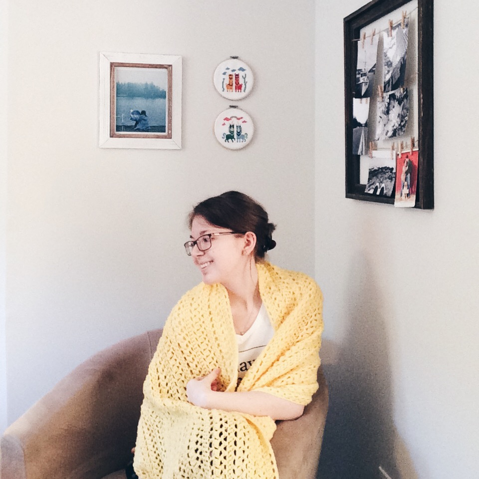 A photo of a young women sitting in a beige bucket chair in the corner of a room with grey walls. She is smiling and looking off to the left, her dark blonde hair pulled into a low bun. She is wearing glasses. She is wrapped in a yellow crochet shawl over a white v-neck shirt with black writing with one arm resting on the armrest of the chair. On the wall behind her to the left, there is a big white wooden frame with a natural wood centre. In the frame is a photo of a girl holding a map infant of a foggy lake. Beside the frame are two small cross-stitches in hoops; one with a pink and a yellow llama standing between two green cacti. The other is of a green and a yellow unicorn with a rainbow above them. On the way to the right is a large dark brown wooden frame that is open. It has 3 lines of hemp strings with paper clips, each line with 2 black and white photography prints.