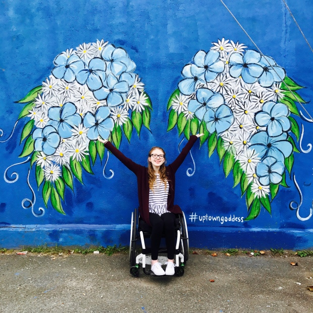 A photo of a young women sitting in her wheelchair in front of a mural. The mural behind her has a blue background and, in the centre, angel wings made of daisies and blue flowers. The wings tips have leaves along their edges. The young girl sitting in her wheelchair with her arms up in the air, reaching for the angel wings. She is smiling. The  subject has blonde hair with pale skin and red lipstick. She is wearing a burgundy cardigan over a black and white striped peplum top and black leggings, and white sneakers. Her wheelchair is white and low-profile.