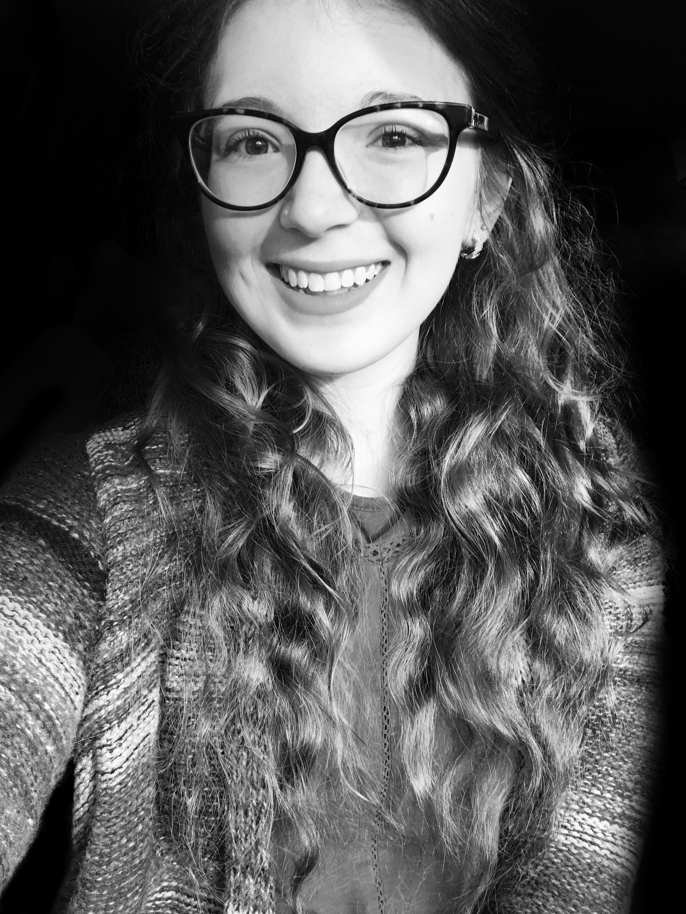 A black and white portrait of a young women seen from the waist up. She has vintage cat-eye style glasses with long wavy hair hanging below her chest. She is wearing a multi-coloured striped cardigan. The subject is holding one arm out toward the camera. The background is solid black.