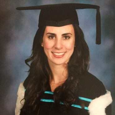 A graduation photo of a young women in front of a blue and grey background. Chelsea has light tan skin and dark brown hair. She is wearing a black graduation cap with the tassel on the right. She is also wearing a V-neck graduation robe. Across her chest is a black and aqua strap holding a black cape with a white fur trim around her shoulders. Chelsea is smiling and looking at the camera.