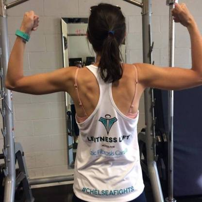 "A photo of a women taken from the back. She is has her arms to her sides bent flexing her biceps and back. Behind her, you can see a squat rack in front of a white cinderblock wall with a long mirror hung on it. Chelsea has her dark brown hair pulled back into a ponytail. Her skin is tan and you can see her back and arm muscles. She is wearing a white racer back tank top that says ""Le Fitness Loft Moves for Cystic Fibrosis Canada"" along with their logo in the middle of the back. Along the hem of the tank top is is written ""#ChelseaFights"" in aqua blue."