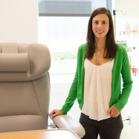 A photo of a young women with tan skin and brown hair, wearing a green cardigan over a white flow tank top and dark grey pants. Chelsea has her left hand in her pocket with her thumb sticking out and her right hand resting on the arm of a beige infusion chair with a wooden tray in front of it. In the background is a window with a grey blind pulled up and bright light coming through. Behind Chelsea, you can see an IV stand with an infusion pump and medication bag plugged into the wall.