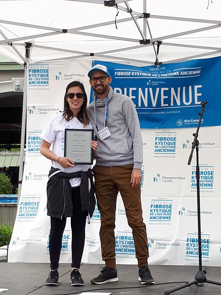 A photo of a young women and your man standing on a stage under a white outdoor tent. The background is a banner welcoming people to an event for Cystic Fibrosis Canada. Chelsea is standing beside the man holding a plaque/award for advocacy. She is wearing a hit shirt, black legging, and black sneakers with a grey sweater tied around her waist. Her skin is tan and her dark brown hair is hanging to above her chest. She is wearing sunglasses. The man beside her is wearing a CF Canada hat and lanyard. He has midtown skin with a dark short beard and rectangle glasses. He is wearing a grey hoodie and brown pants as well as black sneakers.