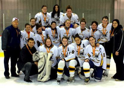 A photo of a women's hockey team and their coaches. They are posed in 3 rows on the ice of a skating rink. In the front row, there are 4 women kneeling, one of them being Chelsea with a Captain badge on her jersey. At the end of the front row and both ends of the second row are coaches wearing black jackets and pants. The team members and their coaches are all wearing medals around their neck. The ribbon of the metals is orange.